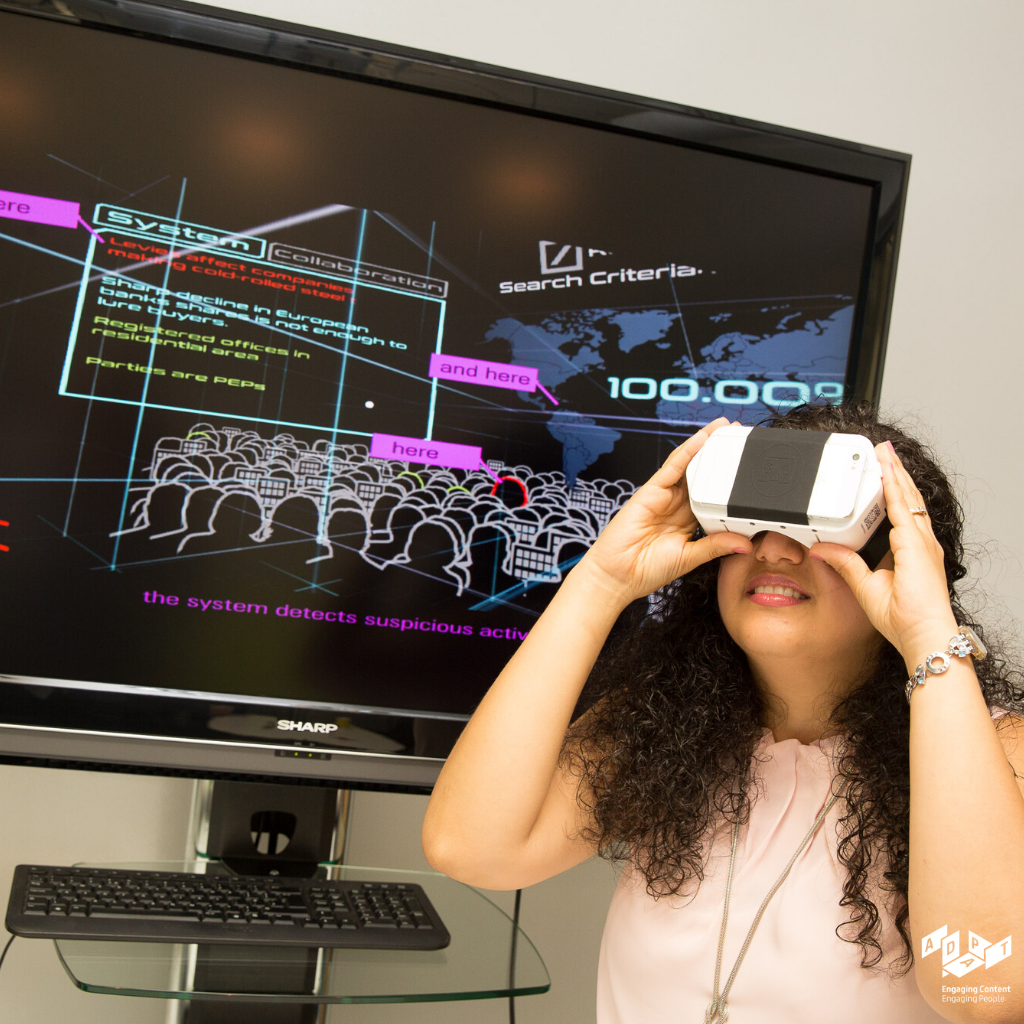 Woman looking up into a virtual reality (VR) headset. Screen behind depicts a VR system