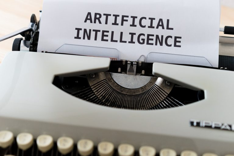 """A typewriter with a sheet of paper that says """"ARTIFICIAL INTELLIGENCE"""""""